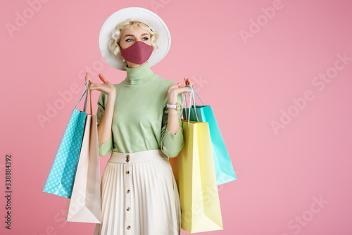Spring shopping during quarantine conception: fashionable woman wearing protective mask posing with colorful paper bags Fototapet