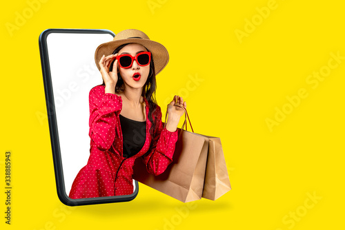 Fotografiet Young attractive asian female holding shopping bag feeling excited, happy and amaze on beauty or fashion online store discount promotion with concept tech on omnichannel e-commerce thru mobile screen