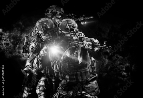 Cuadros en Lienzo American soldiers in combat ammunition with weapons in the hands of equipped laser sights are in battle order