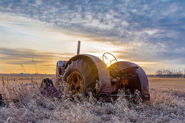 Sunburst at sunset over a vintage tractor abandoned in tall grass on the prairies in Saskatchewan