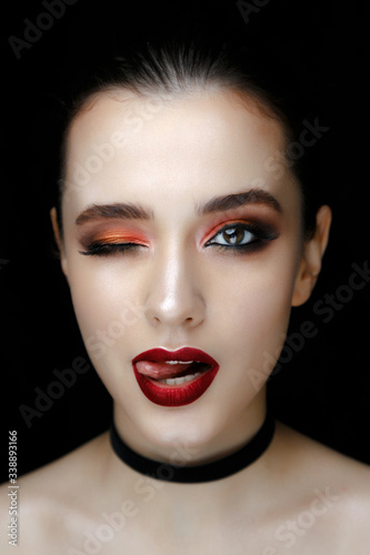 Fototapeta Close-up portrait of gorgeous young woman with red lips and bright makeup of eyes looks to the camera.. Beautiful girl with a healthy clean skin against black background. obraz na płótnie
