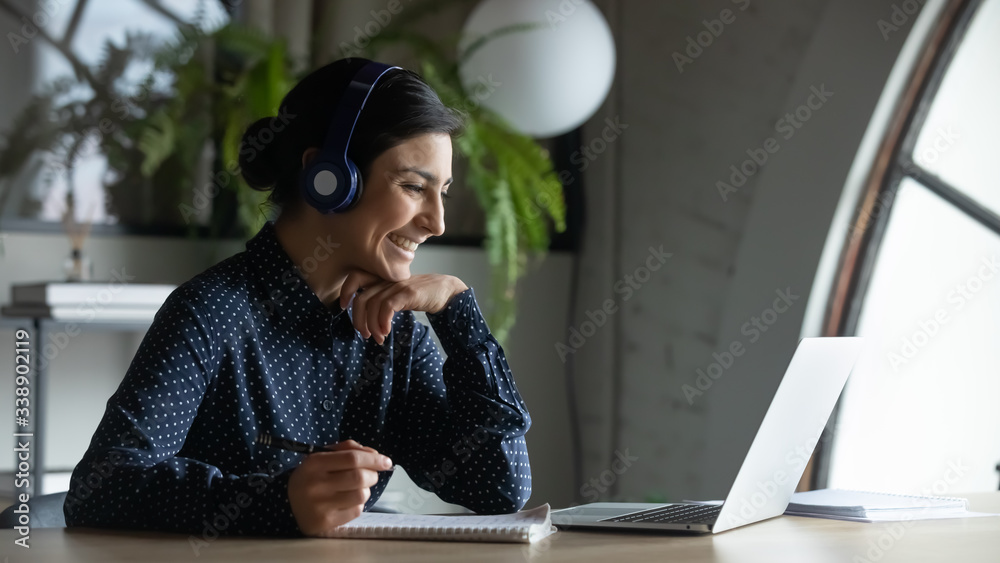 Fototapeta Smiling Indian female employee in wireless earphones talk on video call, have web conference with colleagues, happy ethnic woman worker in headset watch webinar on modern laptop at home