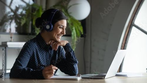 Smiling Indian female employee in wireless earphones talk on video call, have we Fototapeta