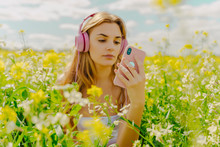 Young Woman With Headphones And Smartphone In A Flower Meadow In Spring
