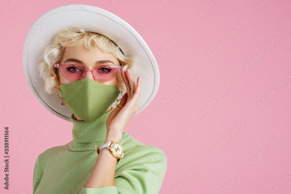 Fototapeta Woman wearing trendy fashion outfit during quarantine of coronavirus outbreak. Model dressed protective stylish handmade face mask, pink sunglasses, white hat, wrist watch, green mint color turtleneck