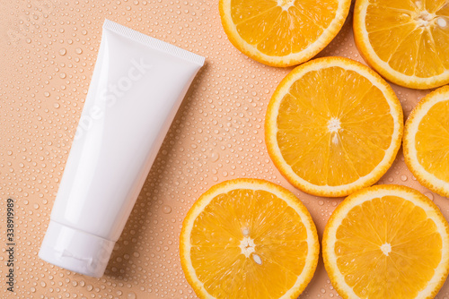 Fototapeta Cream with vitamin c branding concept. Top above overhead close up flatlay view photo of big tube with essential lotion c vitamin isolated over beige background with empty copy blank space obraz