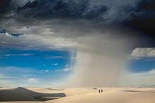 Rain Falls Across The Desert As People Hike