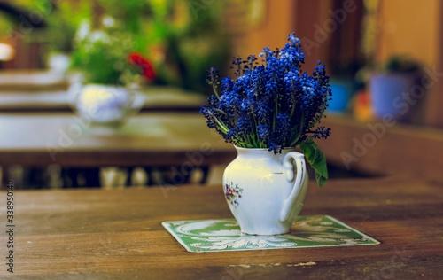 Fototapeta Vase With Blue Flowers On Table obraz na płótnie