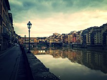 Ponte Vecchio Over Arno River Amidst Buildings Against Cloudy Sky