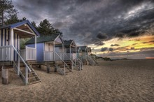 Log Cabins On Beach Against Cloudy Sky During Dusk At Wells Next The Sea