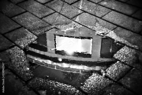 Canvas Print Reflection Of Building In Puddle On Street