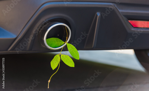 Leinwand Poster Eco electric hybrid car Environmental concept of the green leaf in exhaust muffl