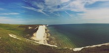 Scenic View Of Sea By Seven Sisters Cliff Against Cloudy Sky