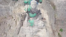 Tilting Up Drone Shot Reveals The Giant Buddha Statue With Bamboo Scaffolding In Construction , Carved Into The Rock Face Of The Hill