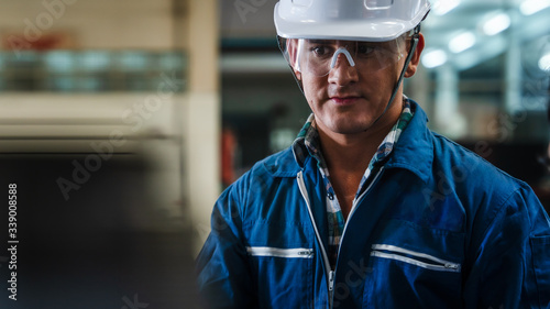 portrait of caucasian man industrial worker or labor in blue factory uniform with white safty helmet in factory metal workshop