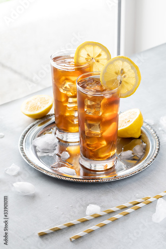 Close up view of two frosty glasses of ice tea beside a window sill with straws in front.