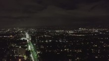 AERIAL: Over Dark Hollywood Los Angeles At Night View On Wilshire Blvd With Clouds Over Downtown And City Lights