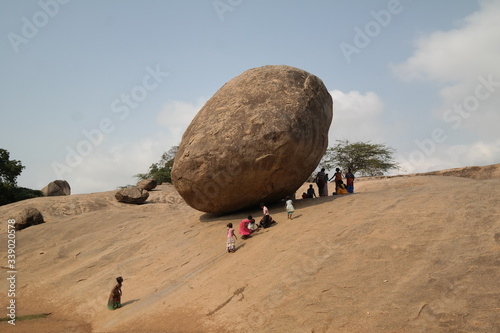 People By Huge Rock On Arid Landscape Against Sky Fototapet