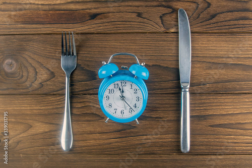 Tela One vintage clock with fork and knife on dark wood table top view