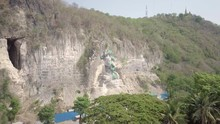 Retreating Aerial Shot Of Green Trees Revealing The Giant Buddha Statue With Bamboo Scaffolding In Construction , Carved Into The Rock Face Of The Hill
