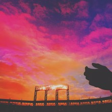 Low Angle View Of Silhouette Hands At Citi Field During Sunset Against Sky
