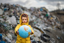 Small Child Holding Globe On Landfill, Environmental Pollution Concept.