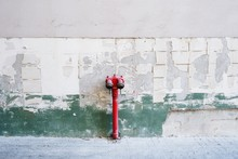 Fire Hydrant Against Weathered Wall