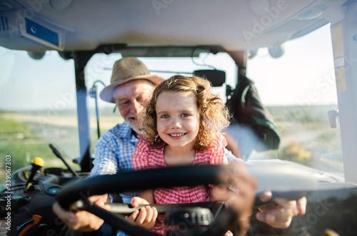 Carta da parati Senior farmer with small granddaughter sitting in tractor, driving