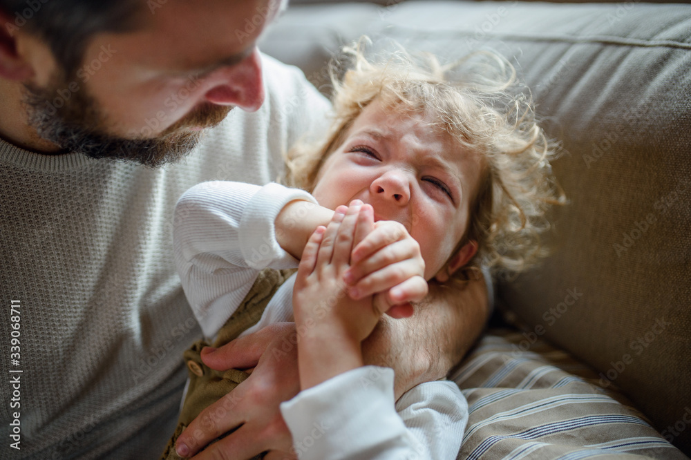 Fototapeta Father with small sick crying toddler daughter indoors at home.