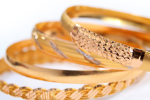 Various Gold Bracelets On A White Background