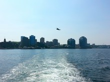 Wake In Sea With Helicopter Flying Over City