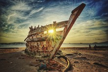 Sunlight In Between Scrap Metal Of Old Abandoned Ship On Beach Against Sky