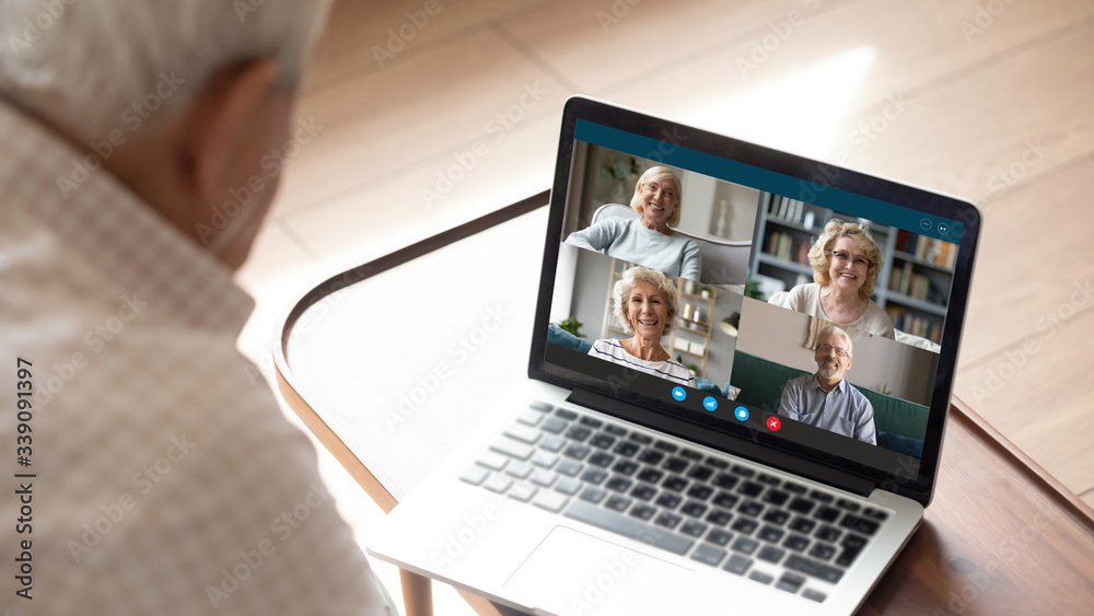 Fototapeta Older generation and modern technologies for virtual visual communication concept. Old man makes videocall talking with relatives or friends by video conference app, pc screen view over male shoulder