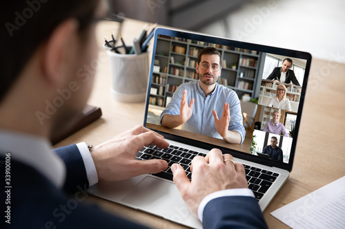 Obraz Businessman boss leader leads distant communication diverse businesspeople involved in group videocall conversation discuss common project, partners negotiating. Modern technology and business concept - fototapety do salonu