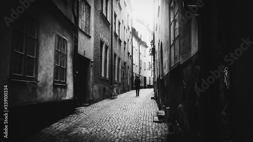Fotografia, Obraz Rear View Of Man Walking On Cobbled Street Amidst Buildings