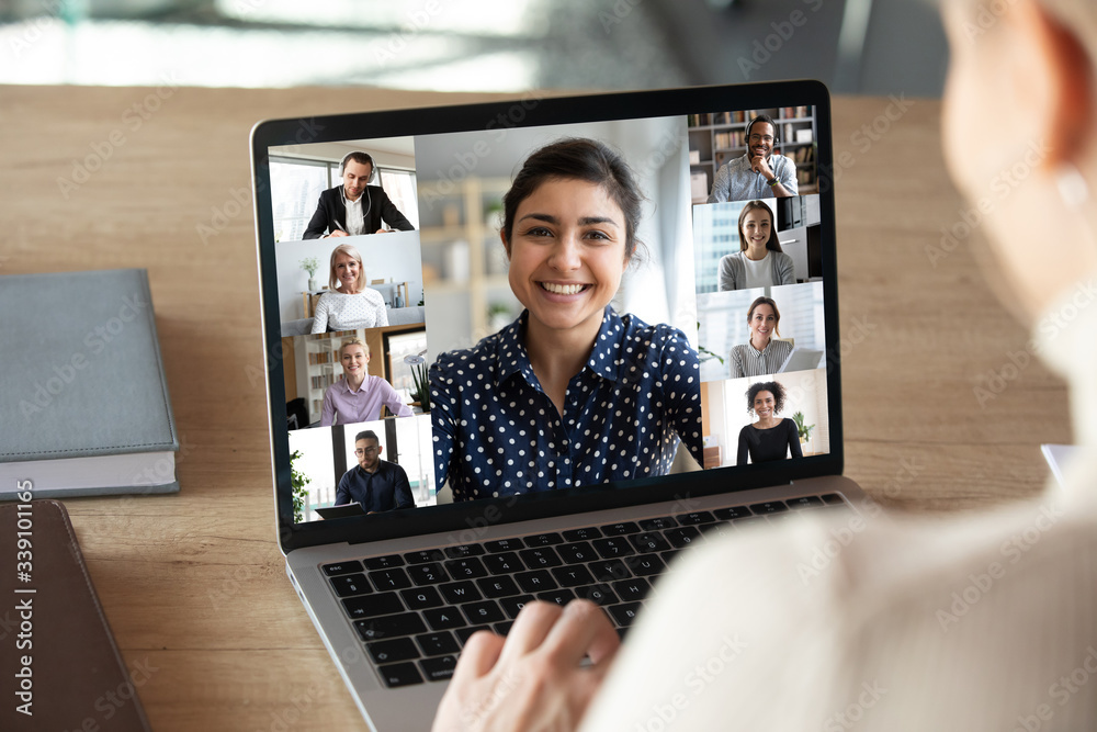Fototapeta Laptop screen over woman shoulder view, indian businesswoman leading videoconference distant communication group videocall conversation. Diverse friends using modern tech enjoy virtual meeting concept