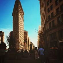 People Walking On Street In Front Of Flatiron Building Against Sky