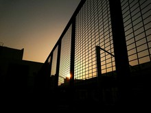 Low Angle View Of Silhouette Metal Fence Against Orange Sunset Sky
