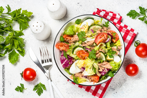 Fototapeta Tuna salad with green leaves, eggs and vegetables. obraz