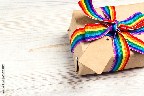 Gift box with rainbow LGBT ribbon and empty tag for inscription on a light wooden background Canvas Print