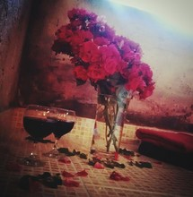 Red Roses In Vase By Wine Glasses