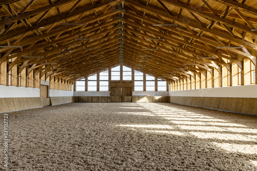 Fototapeta Empty spacious riding hall interior view. Sunlight through windows. Modern equestrian place. obraz