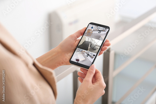 Photo Woman monitoring modern cctv cameras on smartphone indoors, closeup