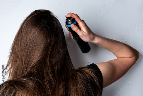 Fototapeta Woman applying dry spray shampoo on her dirty hair. Fast and easy way to keep your hair clean. obraz