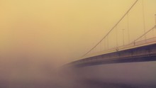 Suspension Bridge Over River During Foggy Weather