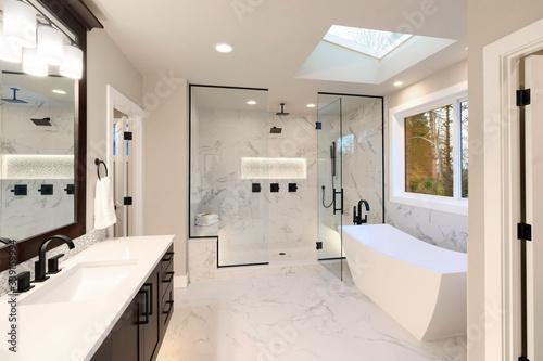 Obraz Luxury modern home bathroom interior with dark brown cabinets, white marble, walk in shower, free standing tub. - fototapety do salonu