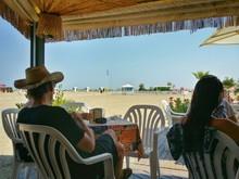 People Relaxing In Gazebo On Beach At Caorle