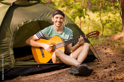 Fotografija Happy young man camping and strum a guitar instrumental music to relax against background of forest sunset