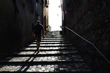 Man Climbing Steep Cobblestone...