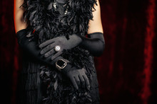 Beautiful Woman Standing In Old Historical 20th Century In Flapper Dress With Fringe, Feathers Boa On Red Background. Details Of Gatsby Costume, Treasure Jewelry.